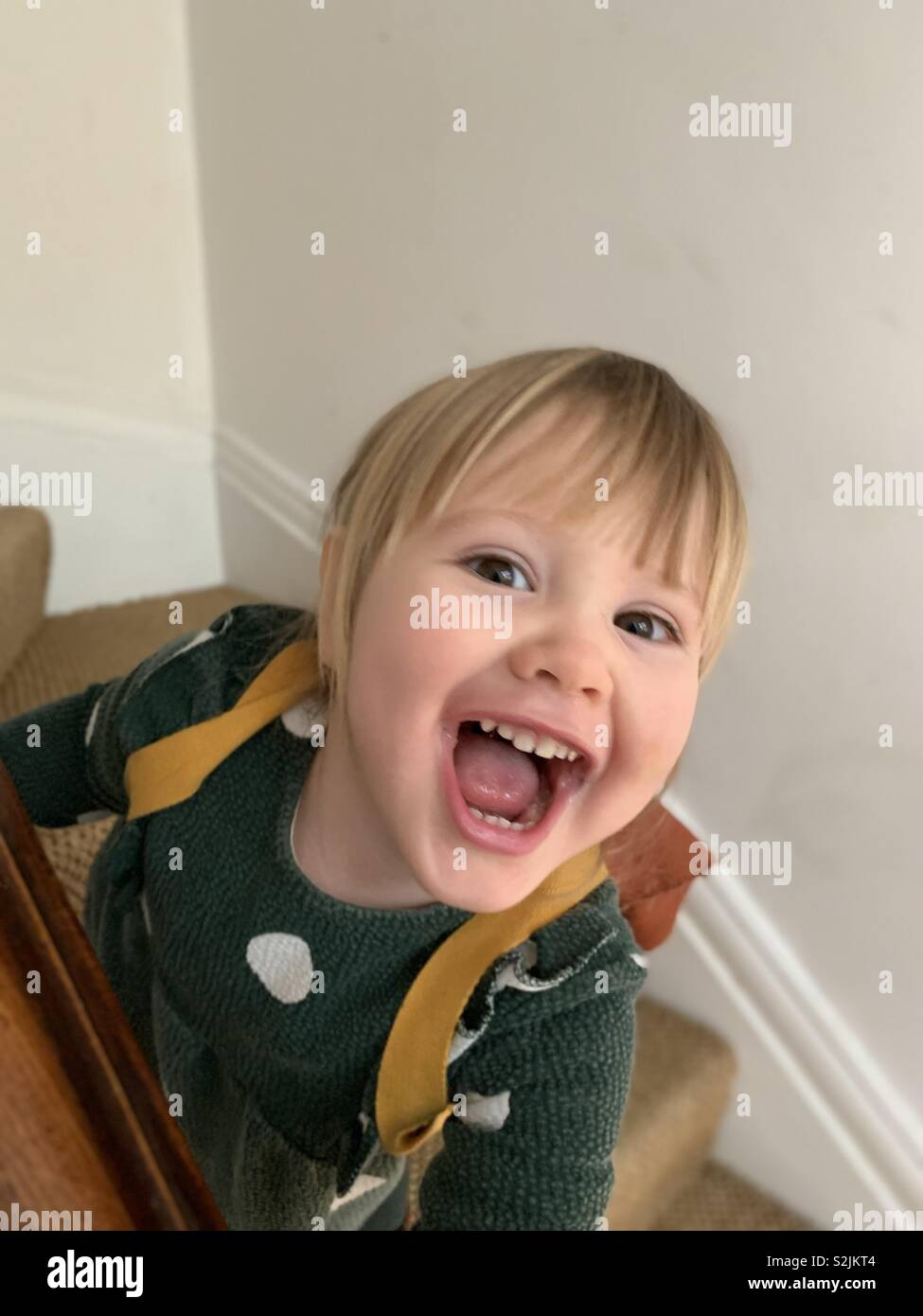 Cheeky little girl grinning - Stock Image