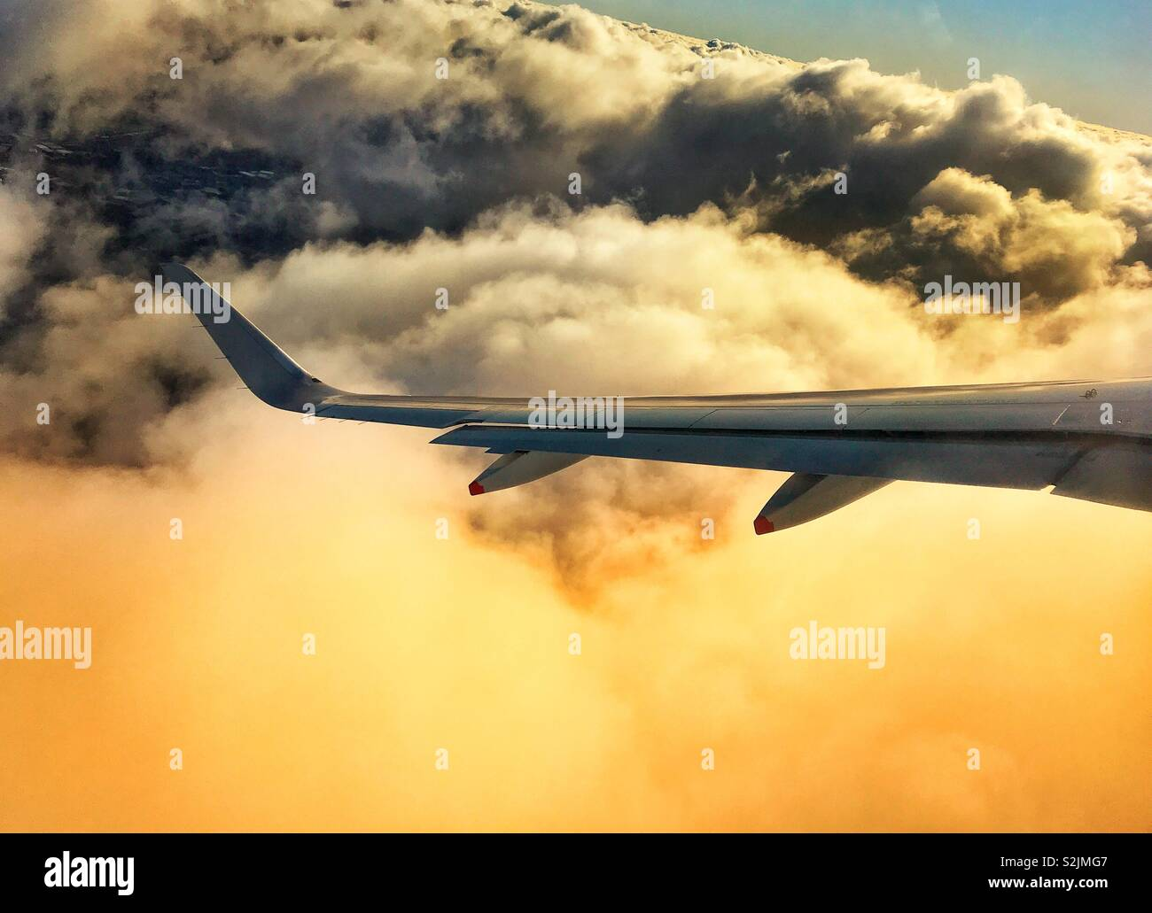Wing of an airliner in flight climbing above stormy clouds - Stock Image