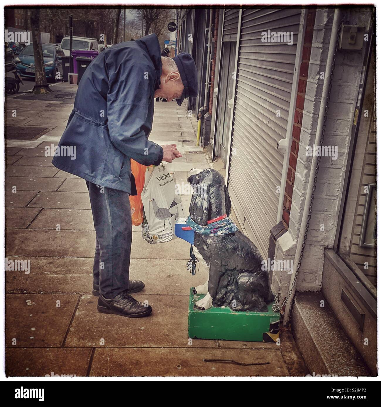 Old man finding change for the RSPCA collection box. - Stock Image