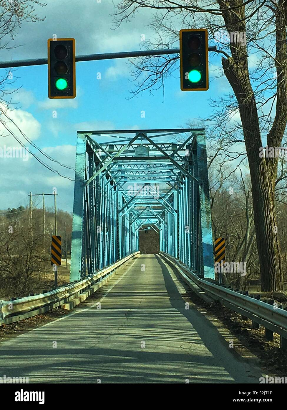 Bridge with one lane and a stoplight that allows only one way traffic to cross the river. - Stock Image