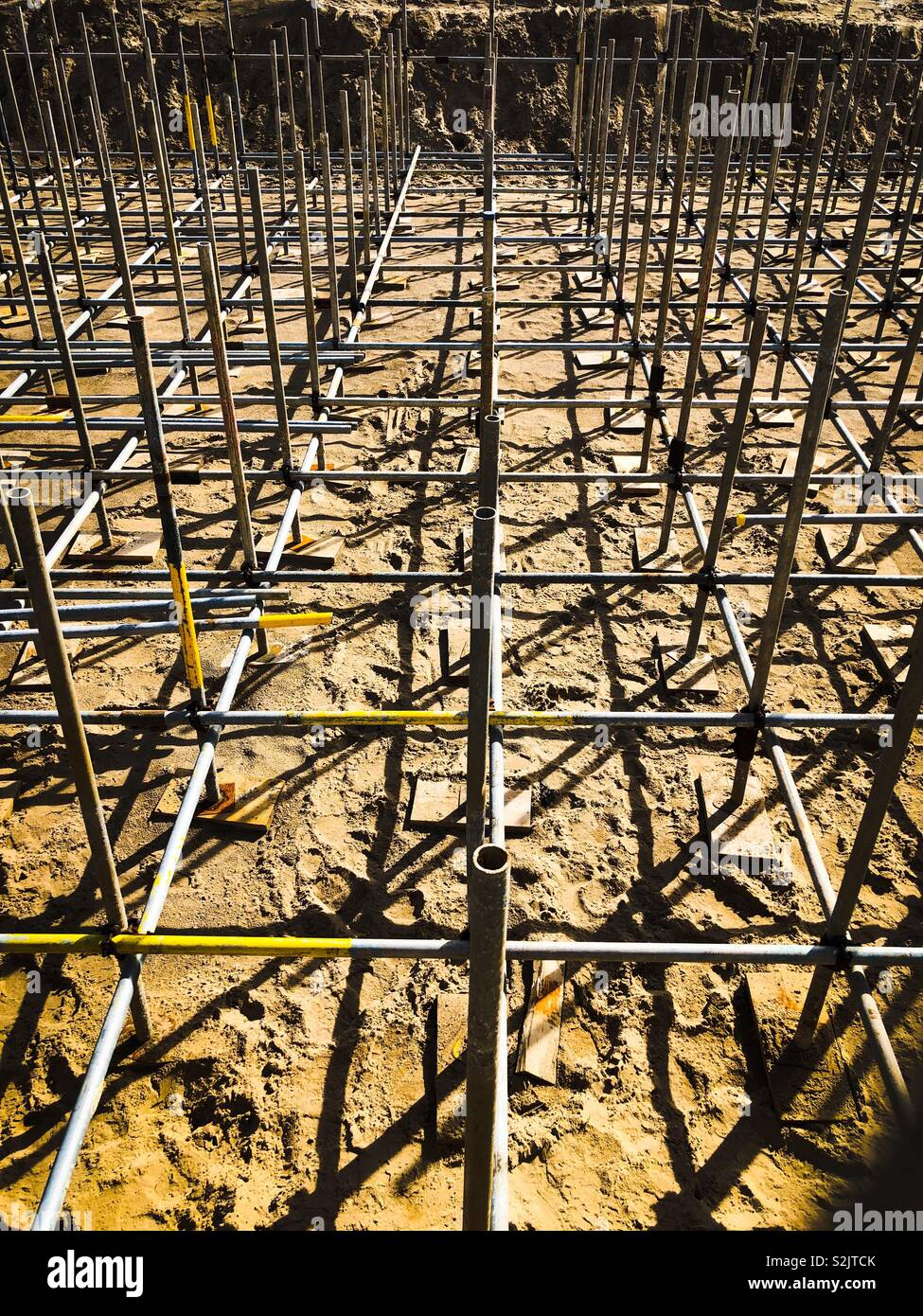 Network of scaffolding on a sandy beach - Stock Image