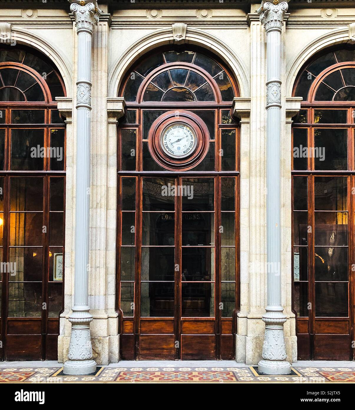 Tall, neoclassic, glazed doors with built in barometer above tiled floor, inside The Stock Exchange Bolsa Palace, at Infante D Henrique Sq, Porto, Portugal - Stock Image