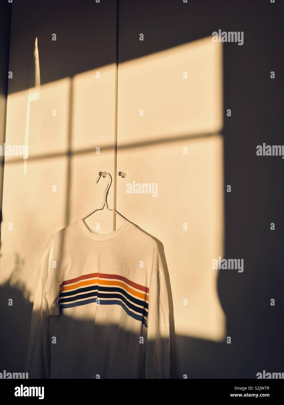 Rainbow sweater hanging on a white wall indoors with sunlight - Stock Image