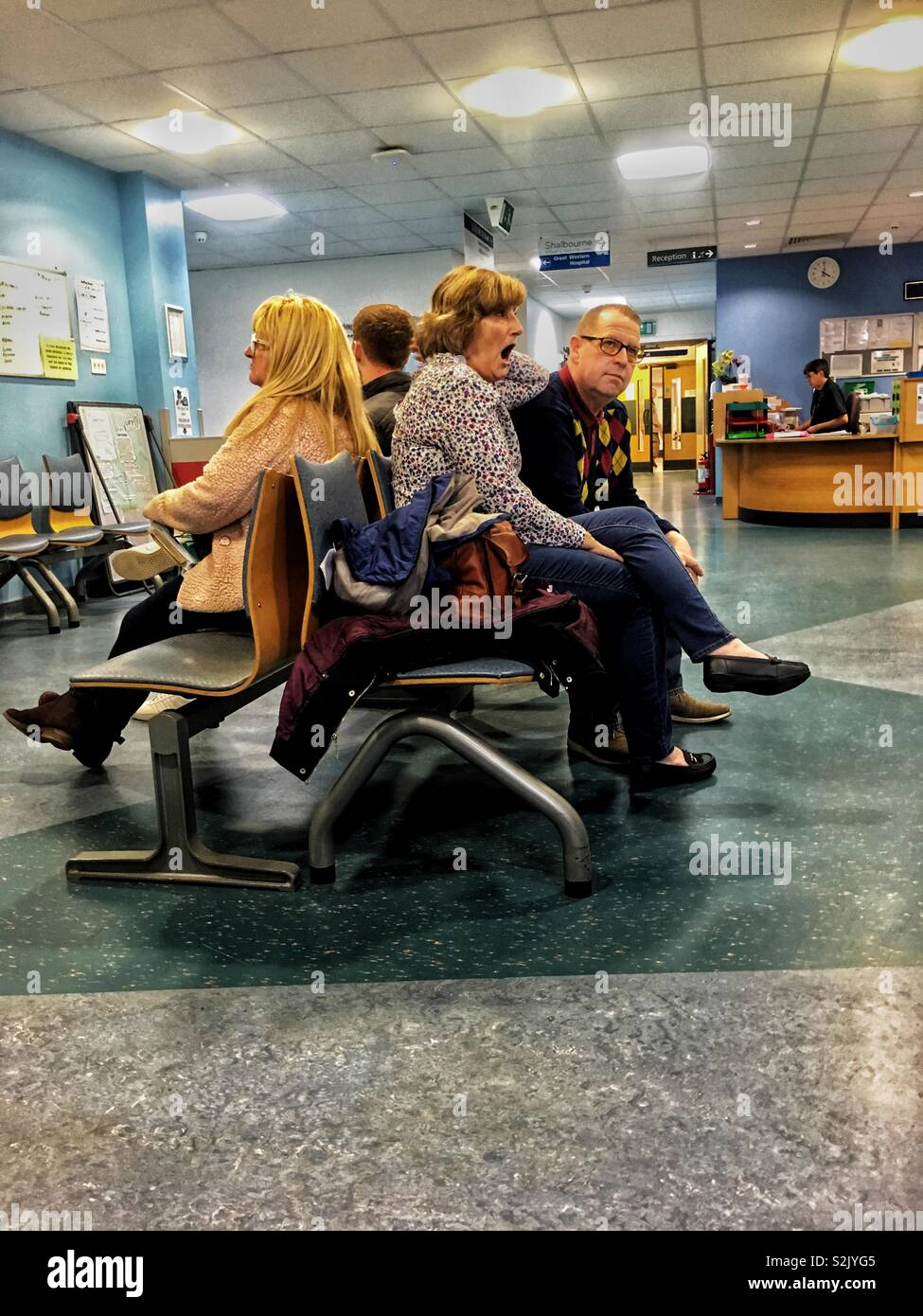 The boredom of people in a hospital waiting area. Woman yawning. - Stock Image