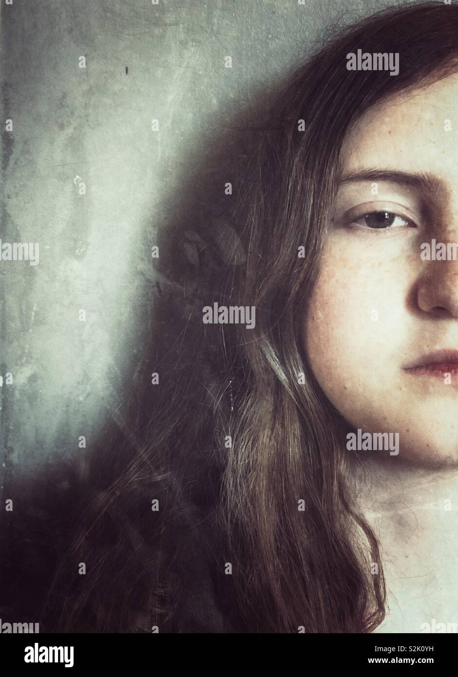 Creative portrait of teenage girl half face with serious expression - Stock Image
