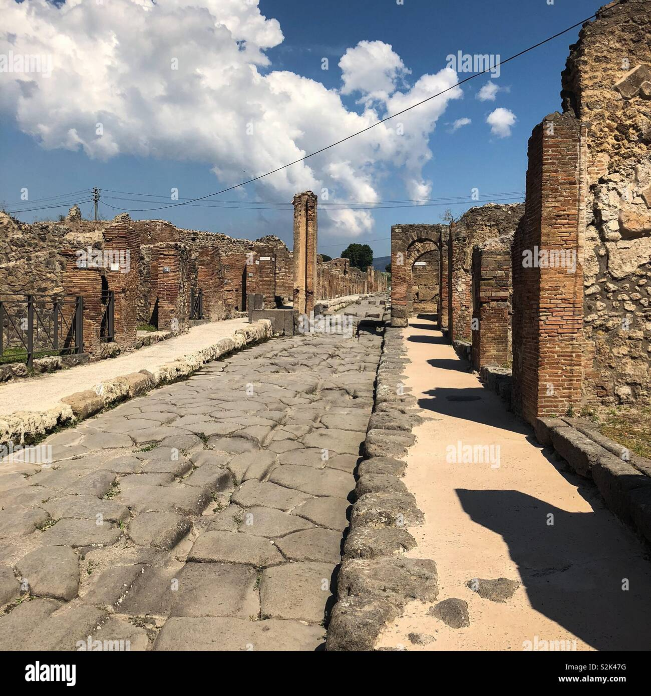 One of the main streets of ancient Pompeii, with ruined walls of town houses but amazingly well preserved paving slabs and pavements - Stock Image