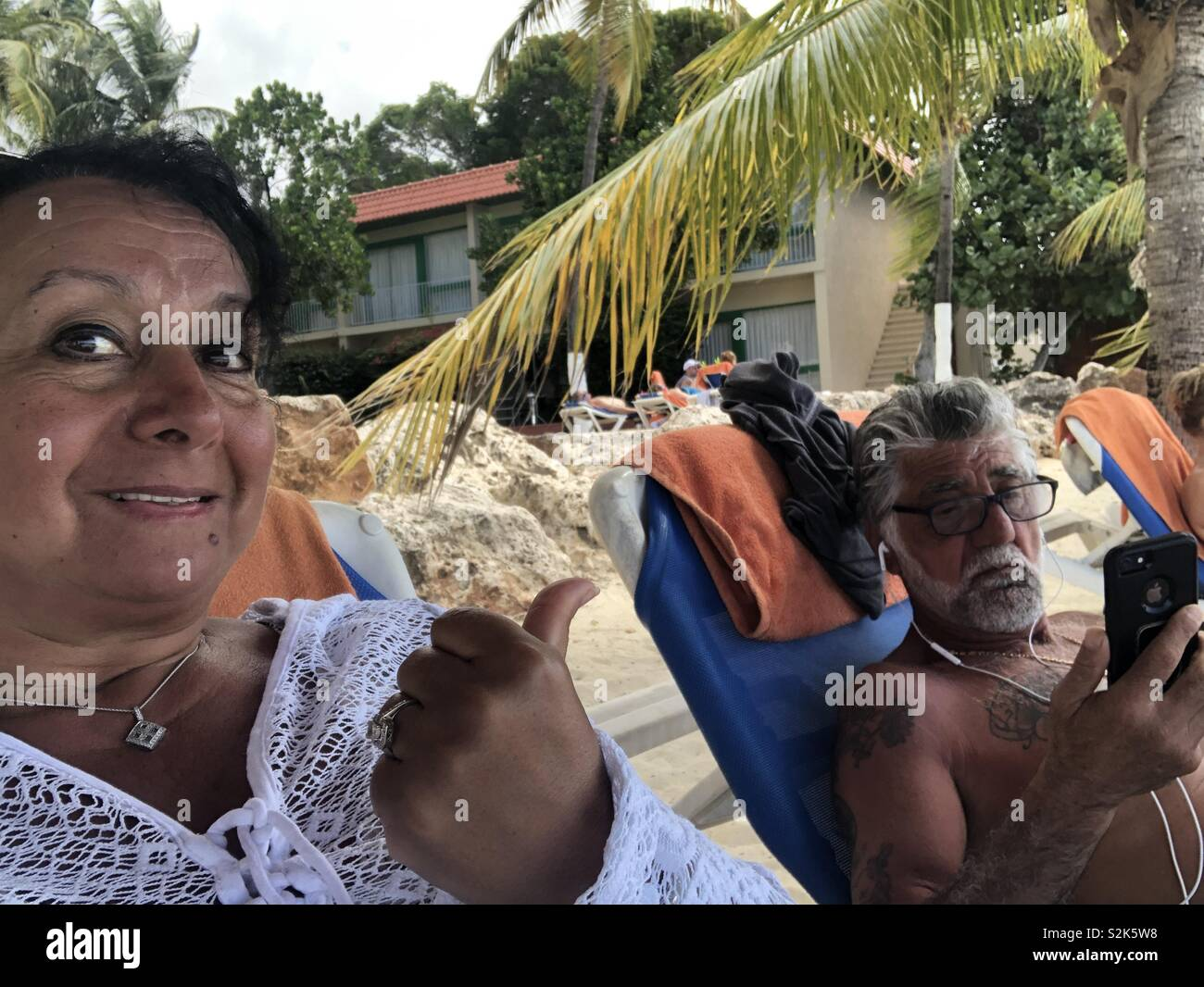 Older couple on beach with husband not paying attention to his wife while consumed on internet - Stock Image
