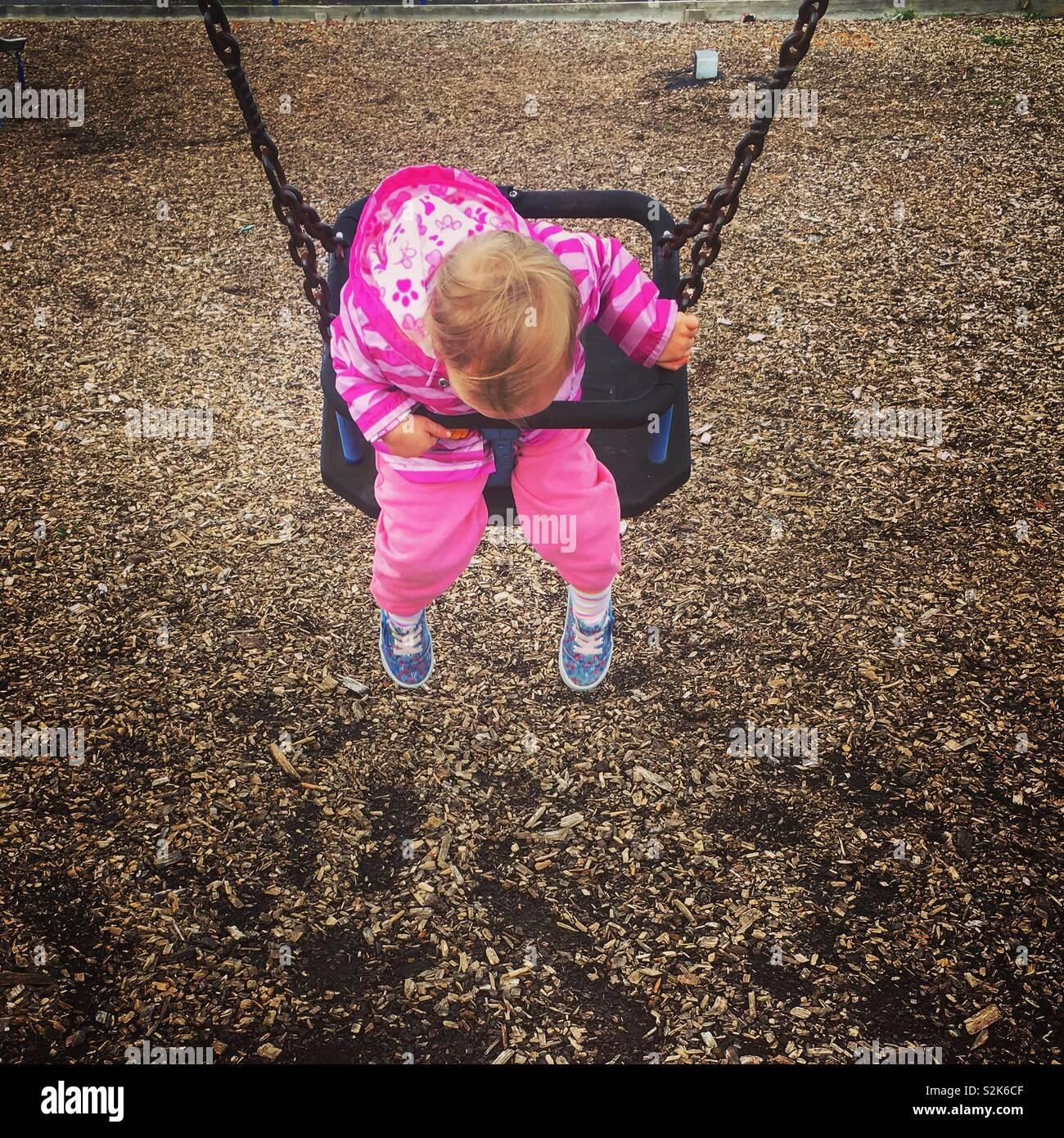 Girl swinging in the park - Stock Image