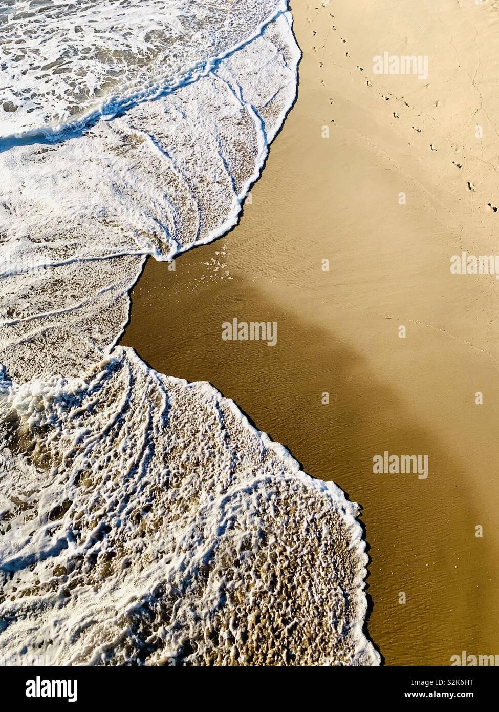 Footprints in the sand at the shoreline. Manhattan Beach, California USA - Stock Image
