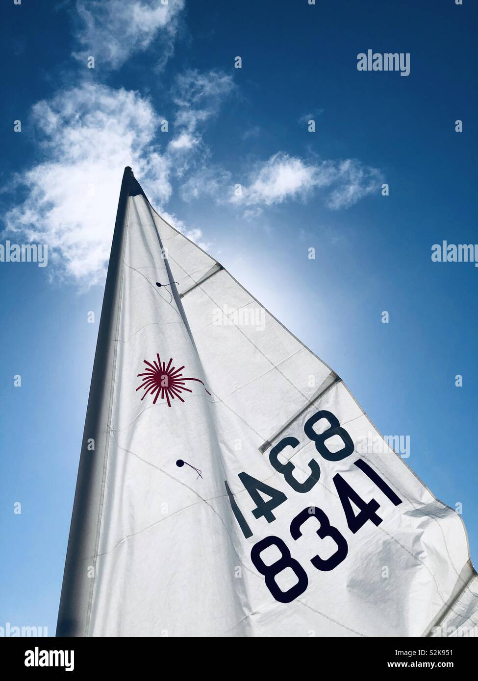 Top of a mainsail backlit by the sun - Stock Image
