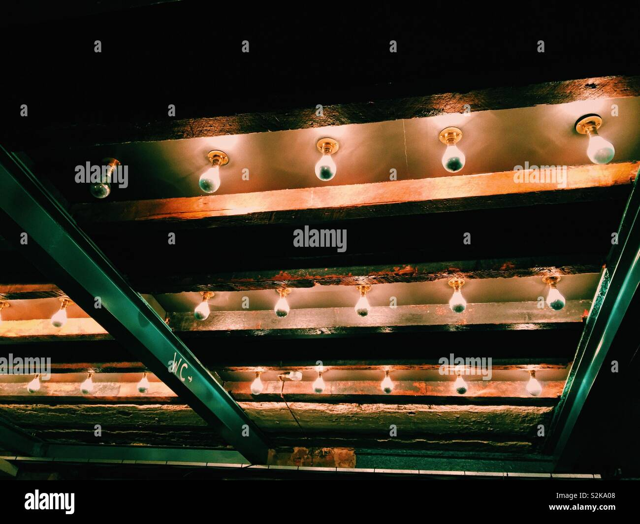 Ceiling with strips of bare bulb lights in restaurant bar. Carnival lights - Stock Image