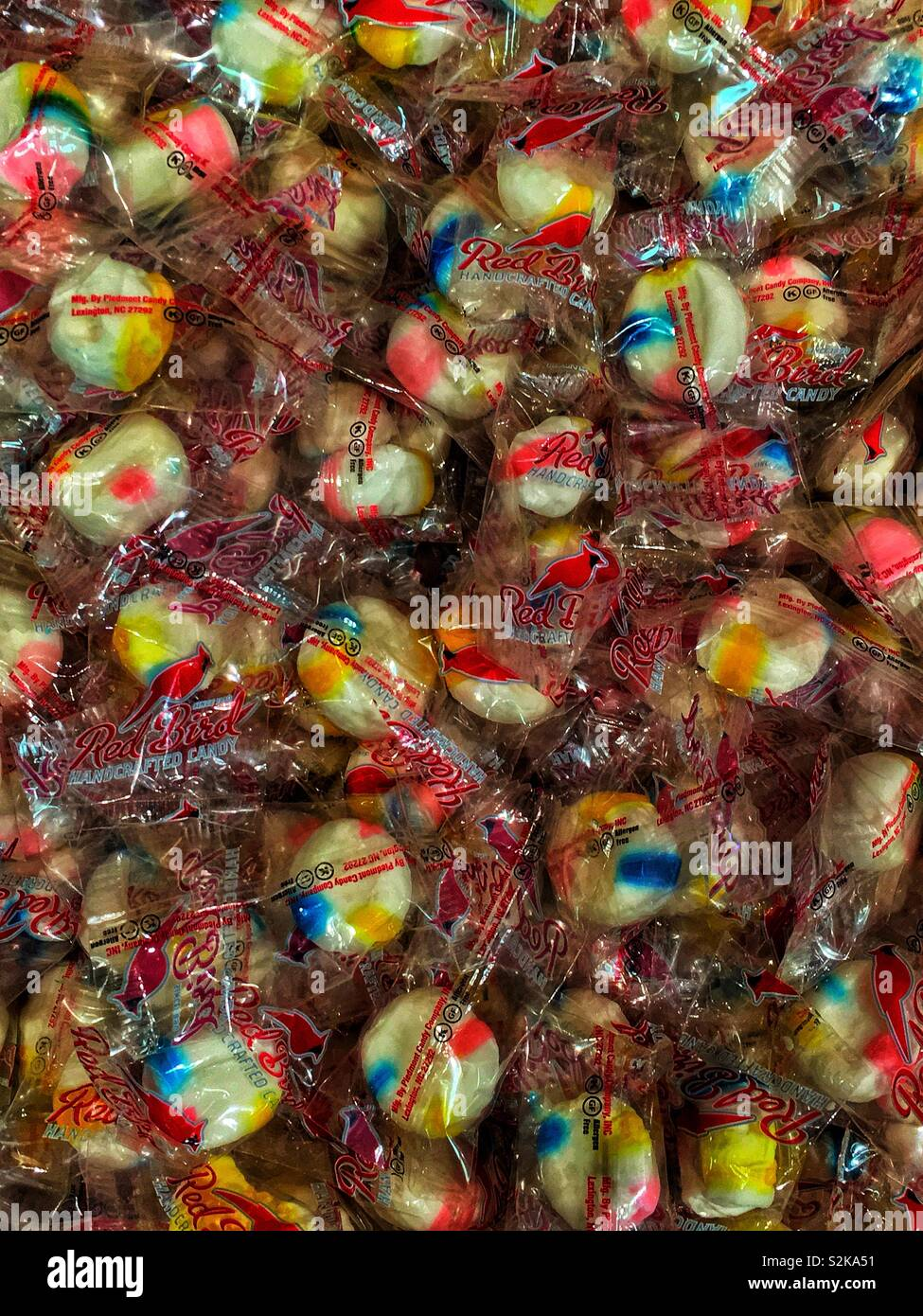 Full frame of Red Bird single wrapped hard candies piled high in a bin for sale. - Stock Image