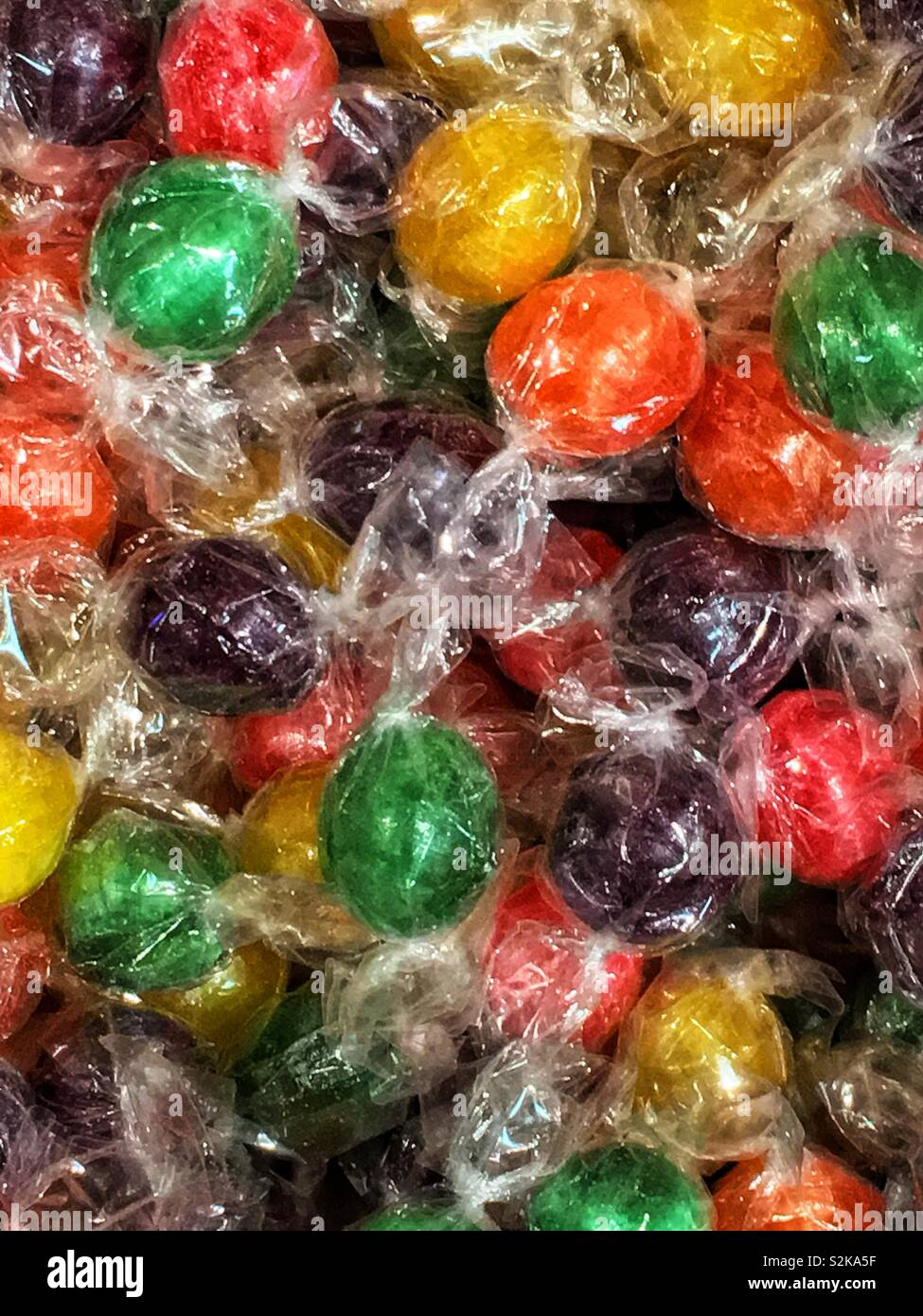 Full frame of green, purple, yellow, and orange individually wrapped hard candies. - Stock Image