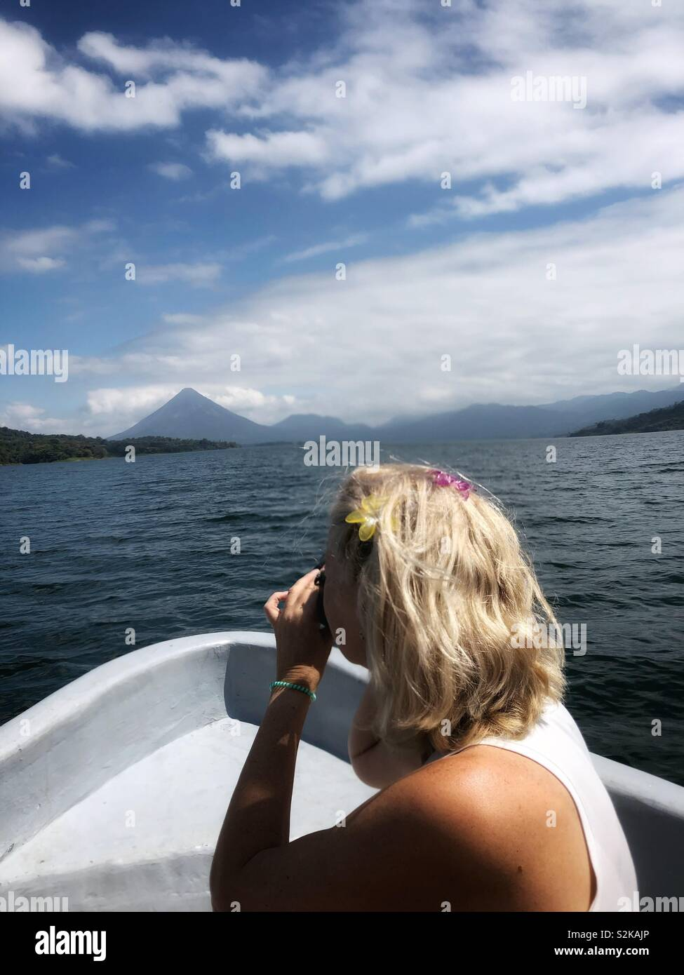 A woman taking photos from a boat on Lake Arenal in Costa Rica. - Stock Image