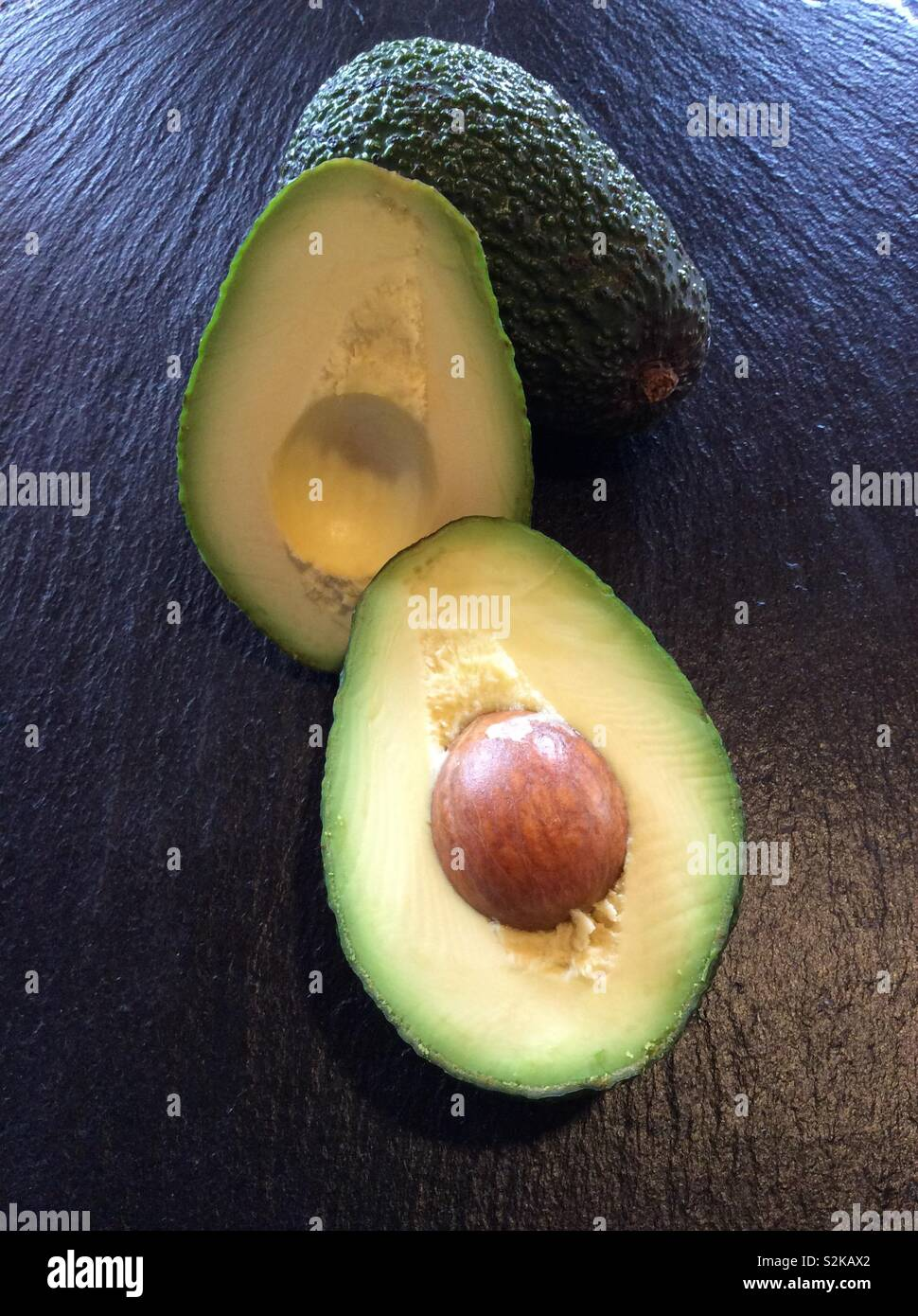 Avocado on black stone background, source of omega 3 from natural food - Stock Image