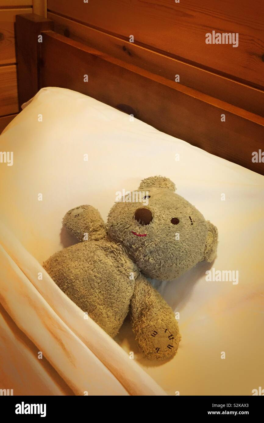 Teddy bear in bed fast asleep.  Tucked in bed for a long comfy cosy sleep.  Hotel room bookings and city break.  Bed and breakfast online internet rooms.  Best prices - Stock Image