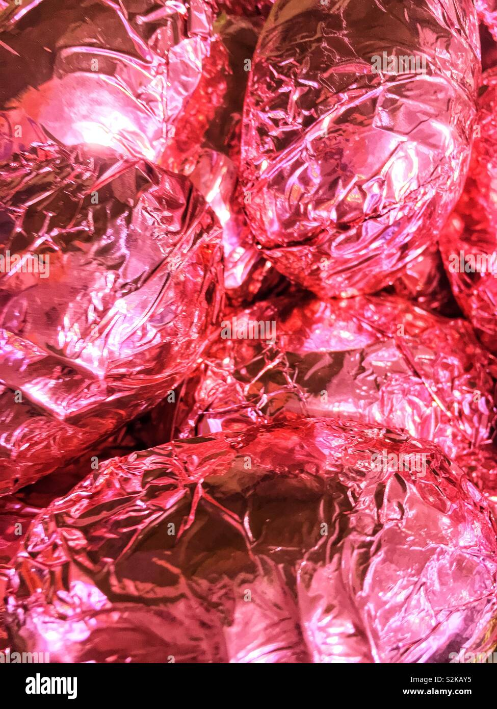 Pink foil wrapped eggs piled in a full frame. - Stock Image