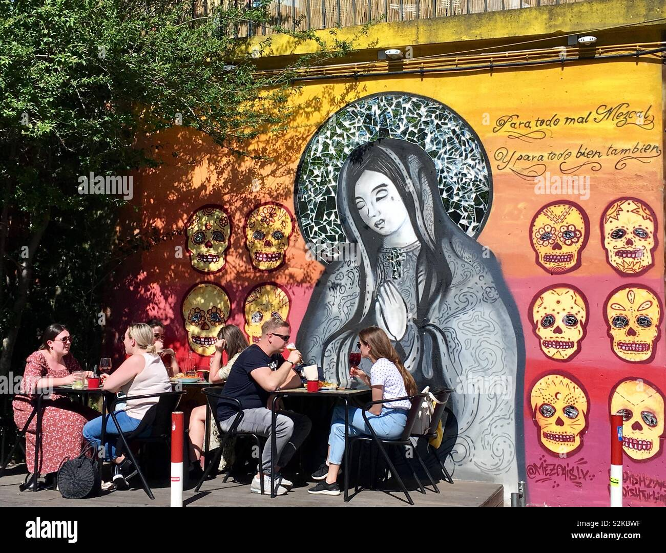 Eating outside surrounded by street art in the local neighbourhood - Stock Image