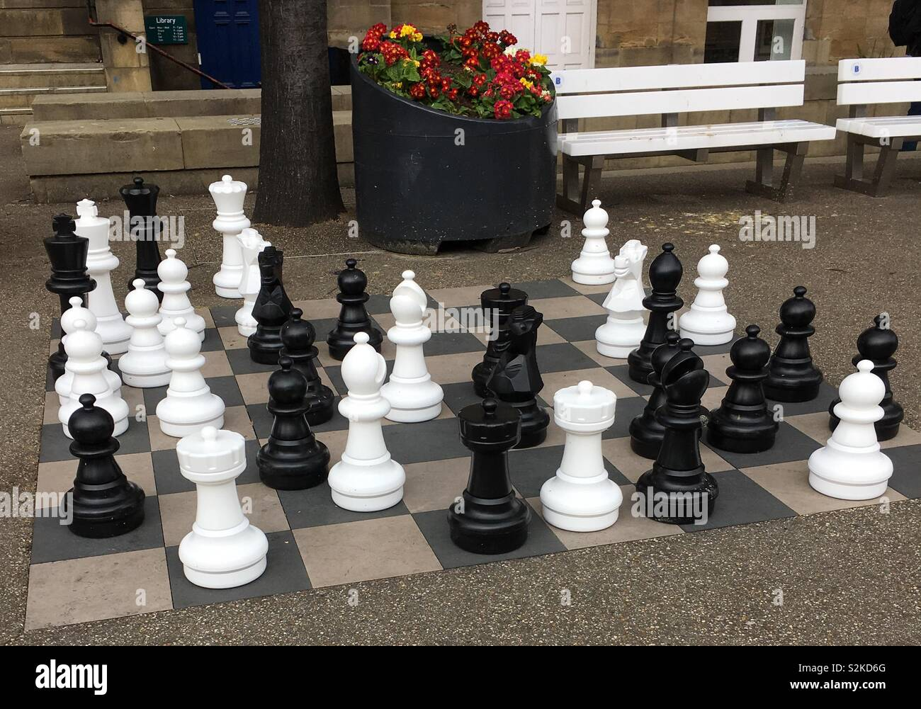 Large outdoor chess game in Victoria Gardens, Leeds, UK, close to the main thoroughfare, The Headrow, and near the Art Gallery, Library and Town Hall. The game is popular in summer when many watch. Stock Photo