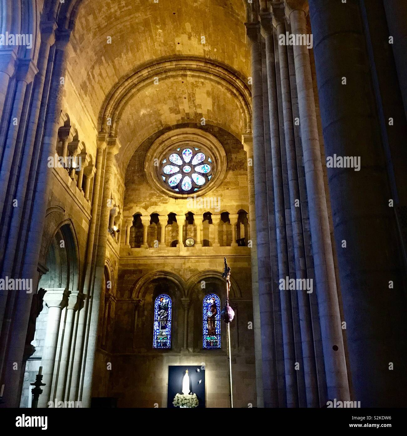 Lisbon cathedral - the cross and stain glass windows against the high ceiling Stock Photo