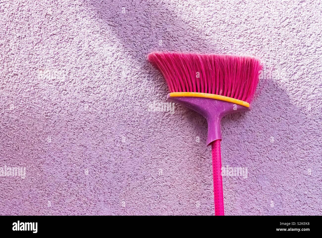 Purple brush against purple wall - Stock Image