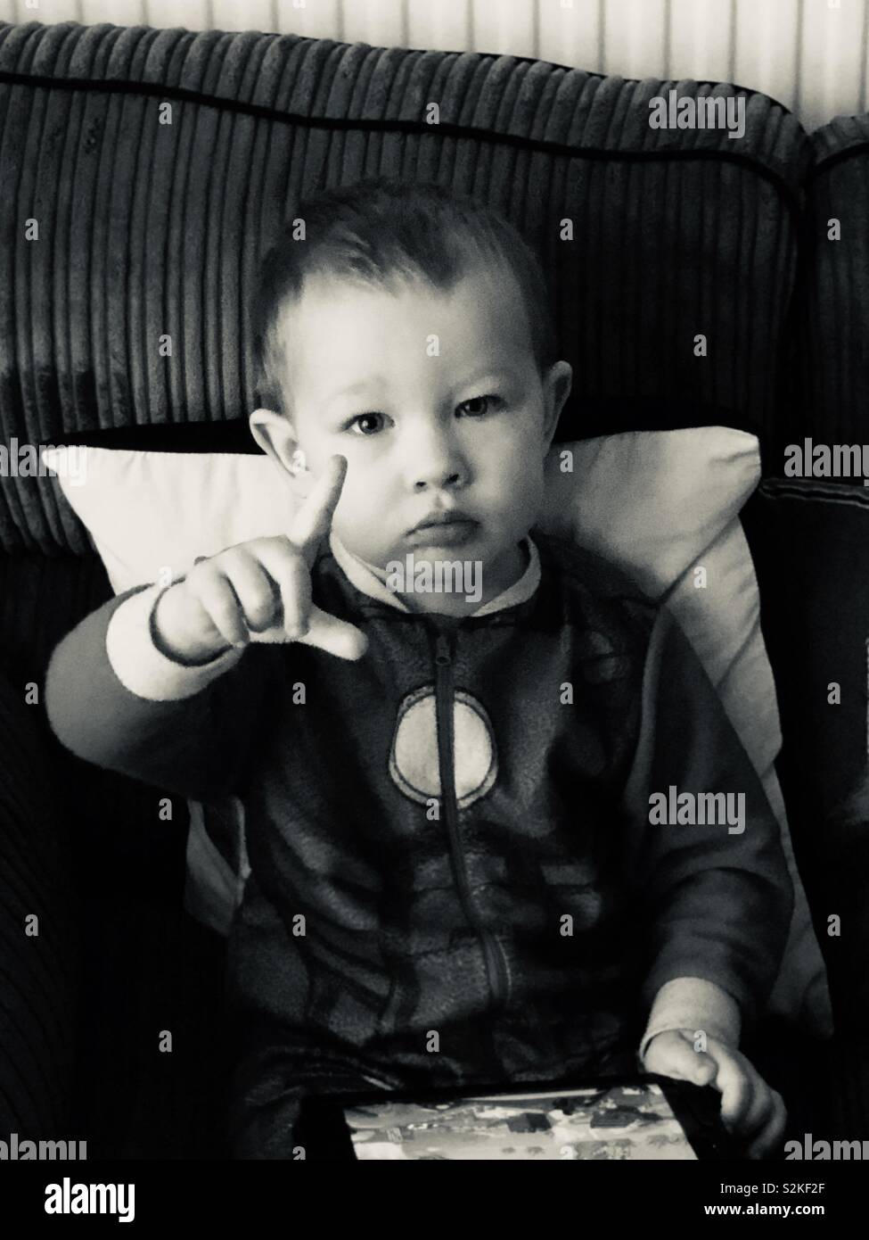 Boy making L loser sign looking serious black and white - Stock Image