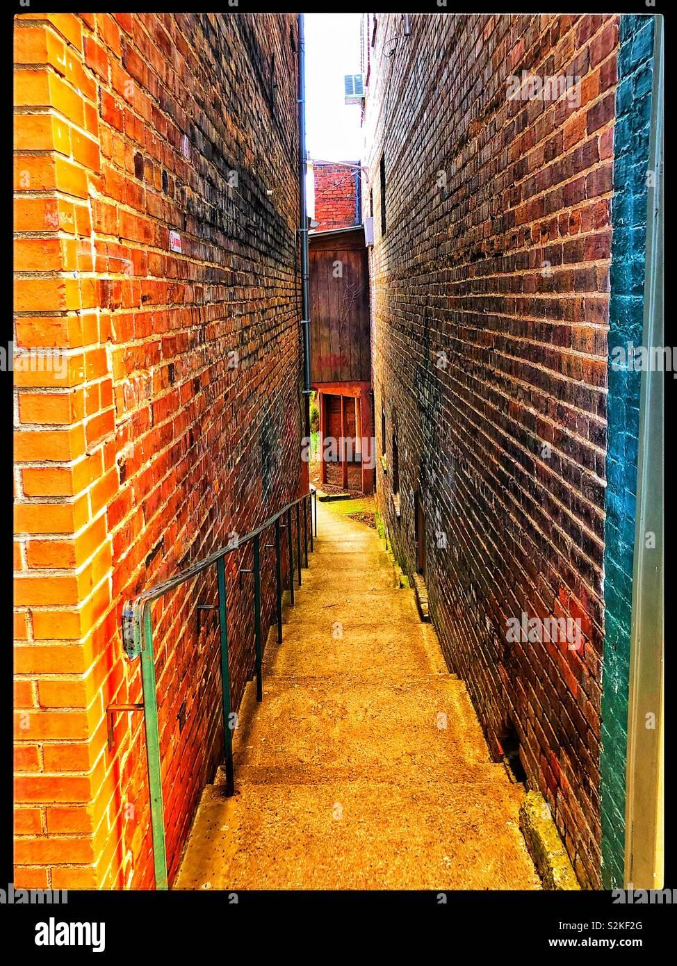 Stairway between two brick buildings - Stock Image