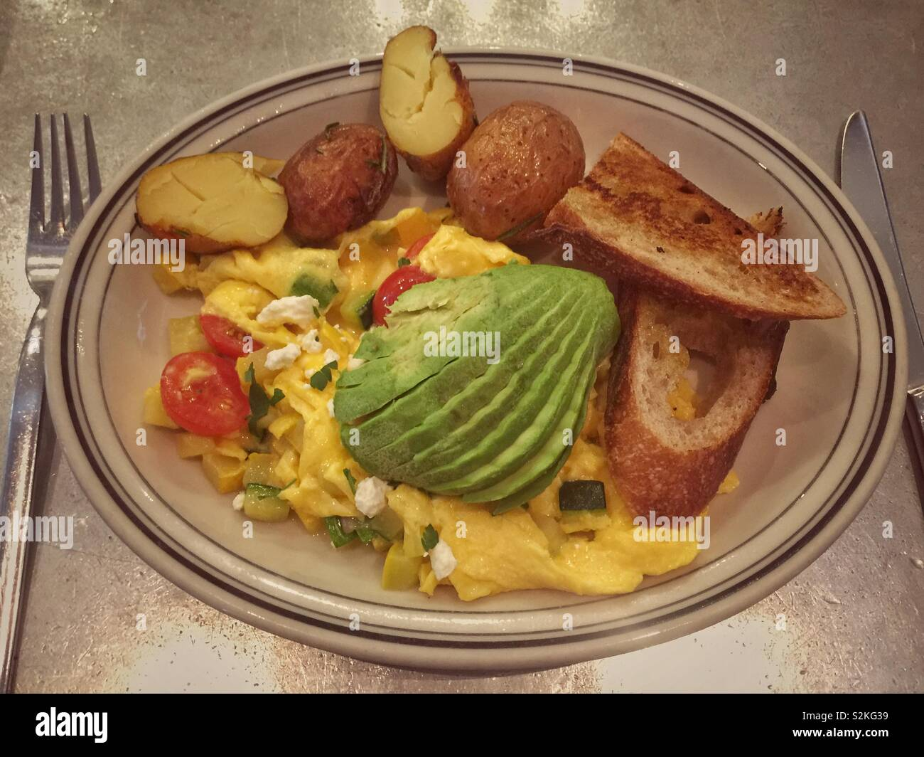 Plate of vegetables scramble eggs with avocado, fried potatoes and toasted bread - Stock Image
