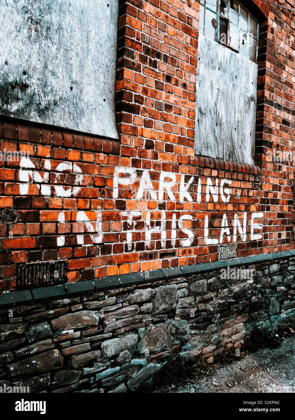 No parking in this lane written on a old red brick wall - Stock Image