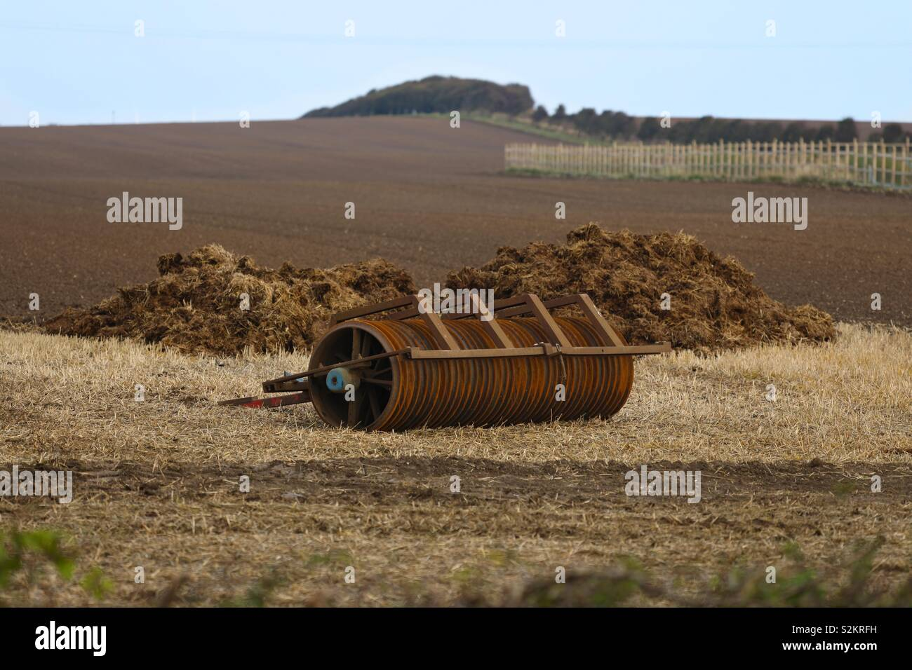 A piece of old farm machinery sits in a field in front of some manure near to Kilnsea, East Riding of Yorkshire Stock Photo