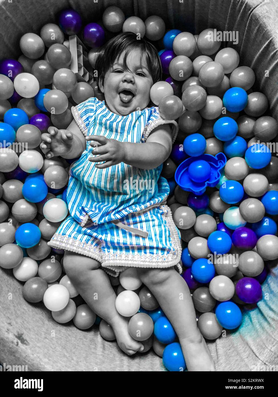 Baby in ball pit - Stock Image