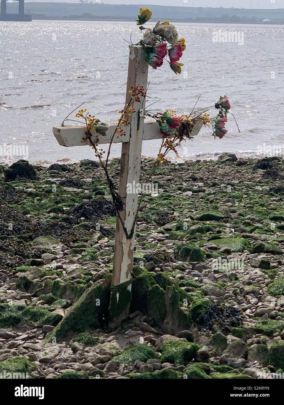 A wooden cross sits in the north mud bank of the River Humber as a memorial to tragic events that have occurred on the river in the past. - Stock Image