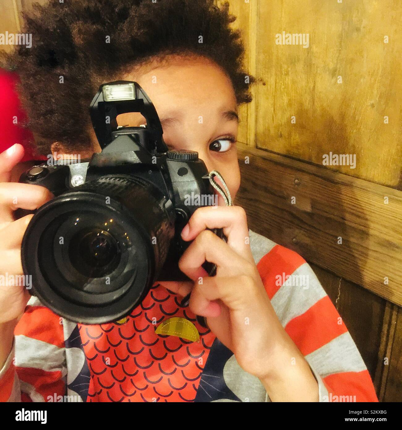 A little boy plays with a camera. - Stock Image