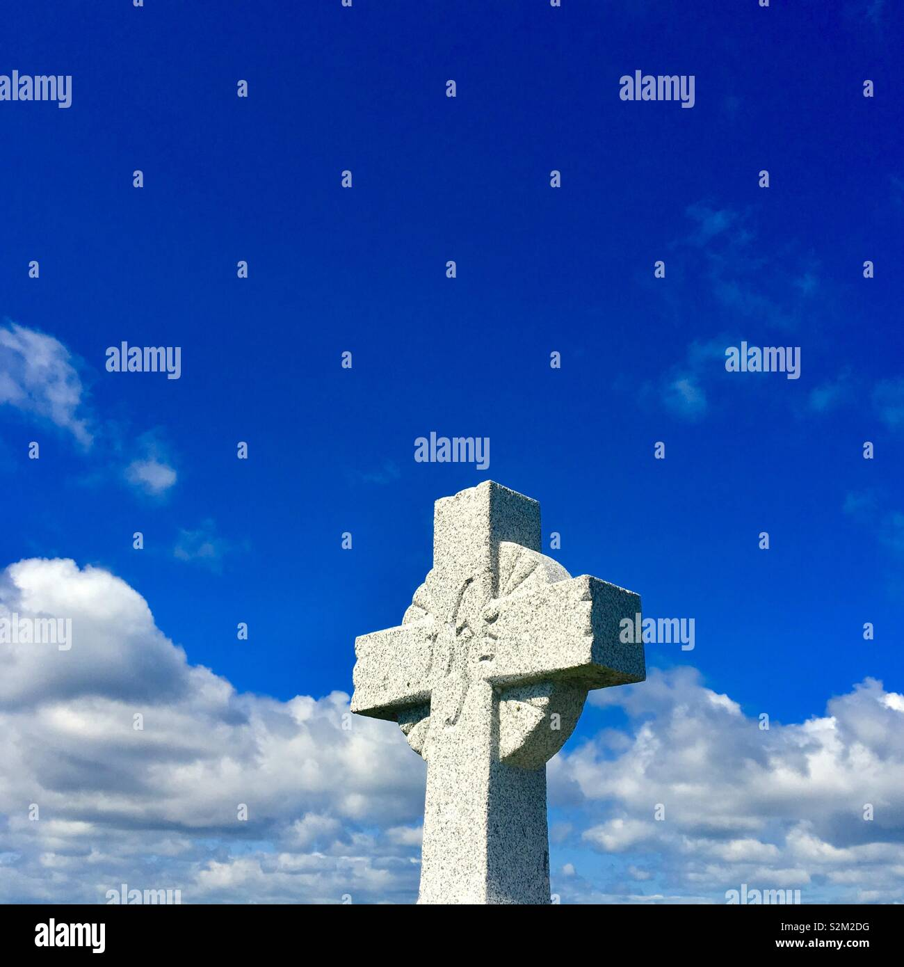 Cross Gravestone with sky in background Stock Photo