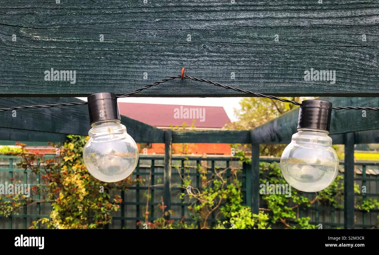 Garden lights hanging from a wooden beam. - Stock Image