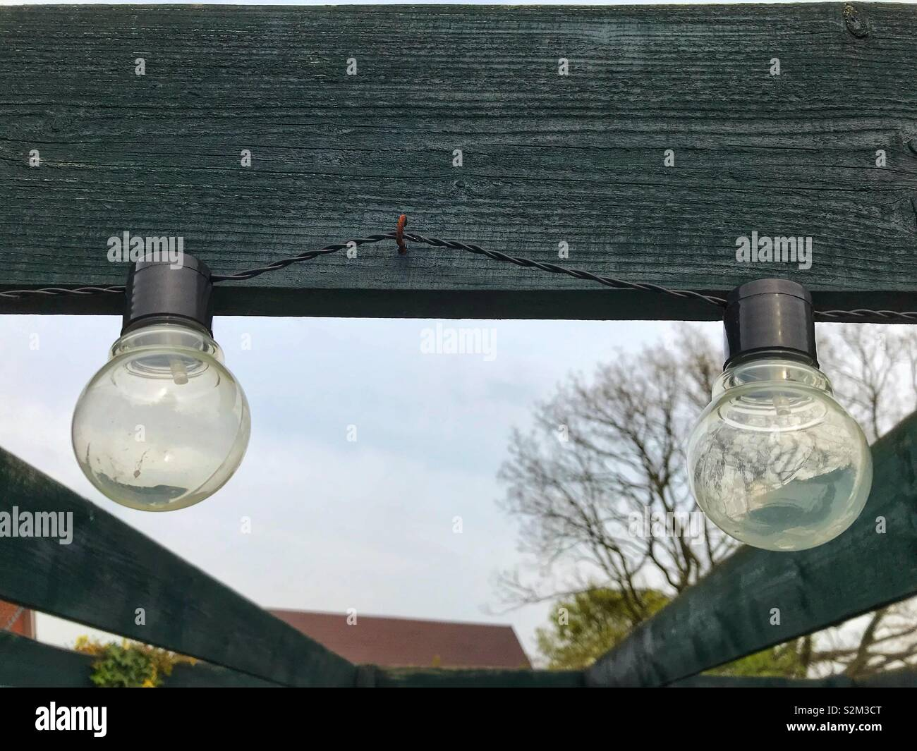 Garden lights hanging from a wooden beam in a garden. - Stock Image