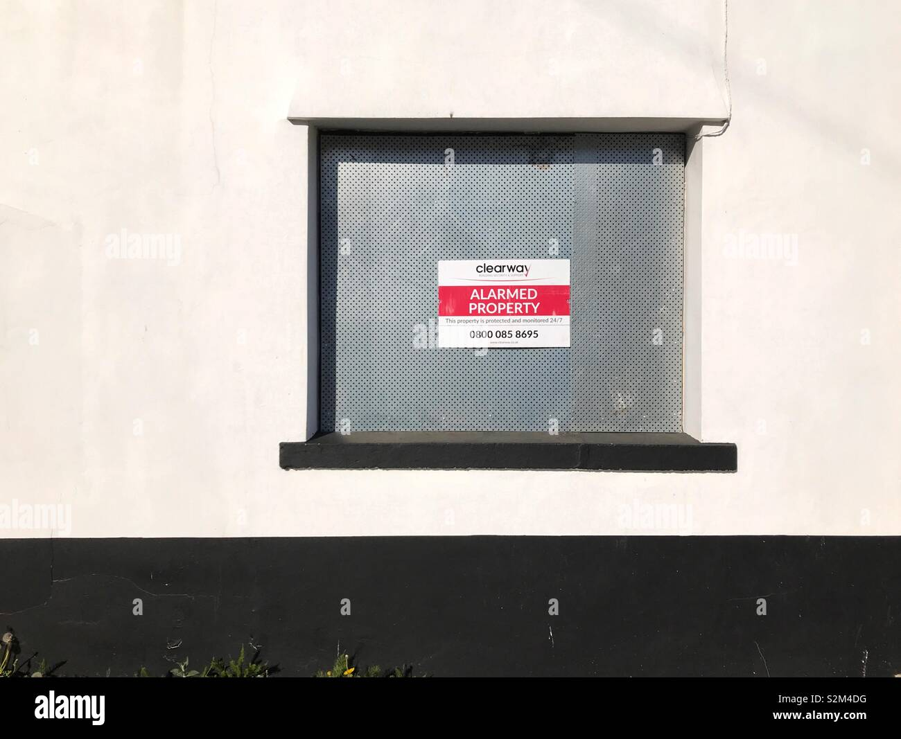 Boarded up window with security notice on a public house which has closed down - Stock Image