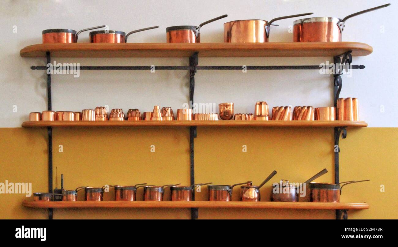 Beautiful copper pots and pans arranged on shelving against a two tone backdrop of yellow and white - Stock Image