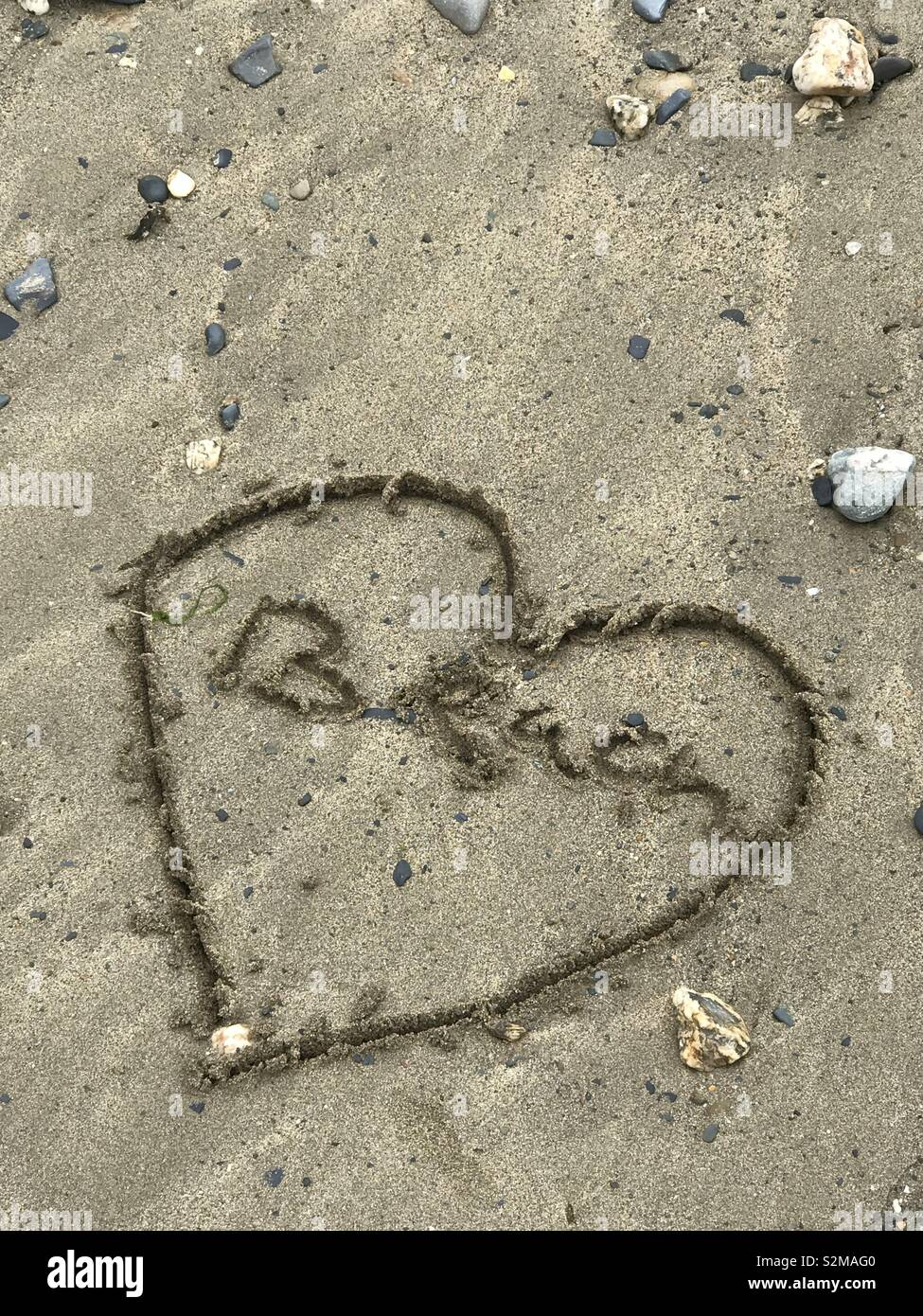 Writing in the sand on the beach - Stock Image