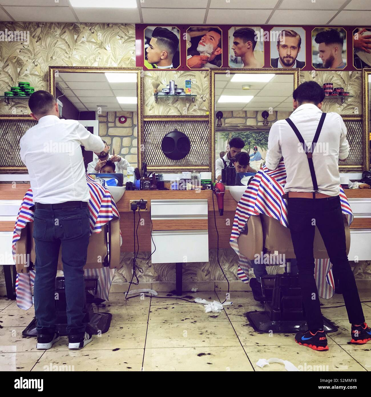 Babrers at work in a barbers shop cutting hair. - Stock Image