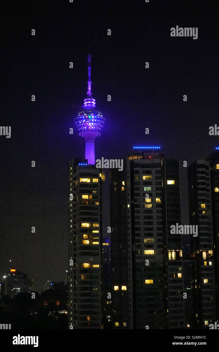 TV Tower, communications tower. Kuala Lumpur, Malaysia. By night, illuminated. Surrounded by apartment buildings. - Stock Image