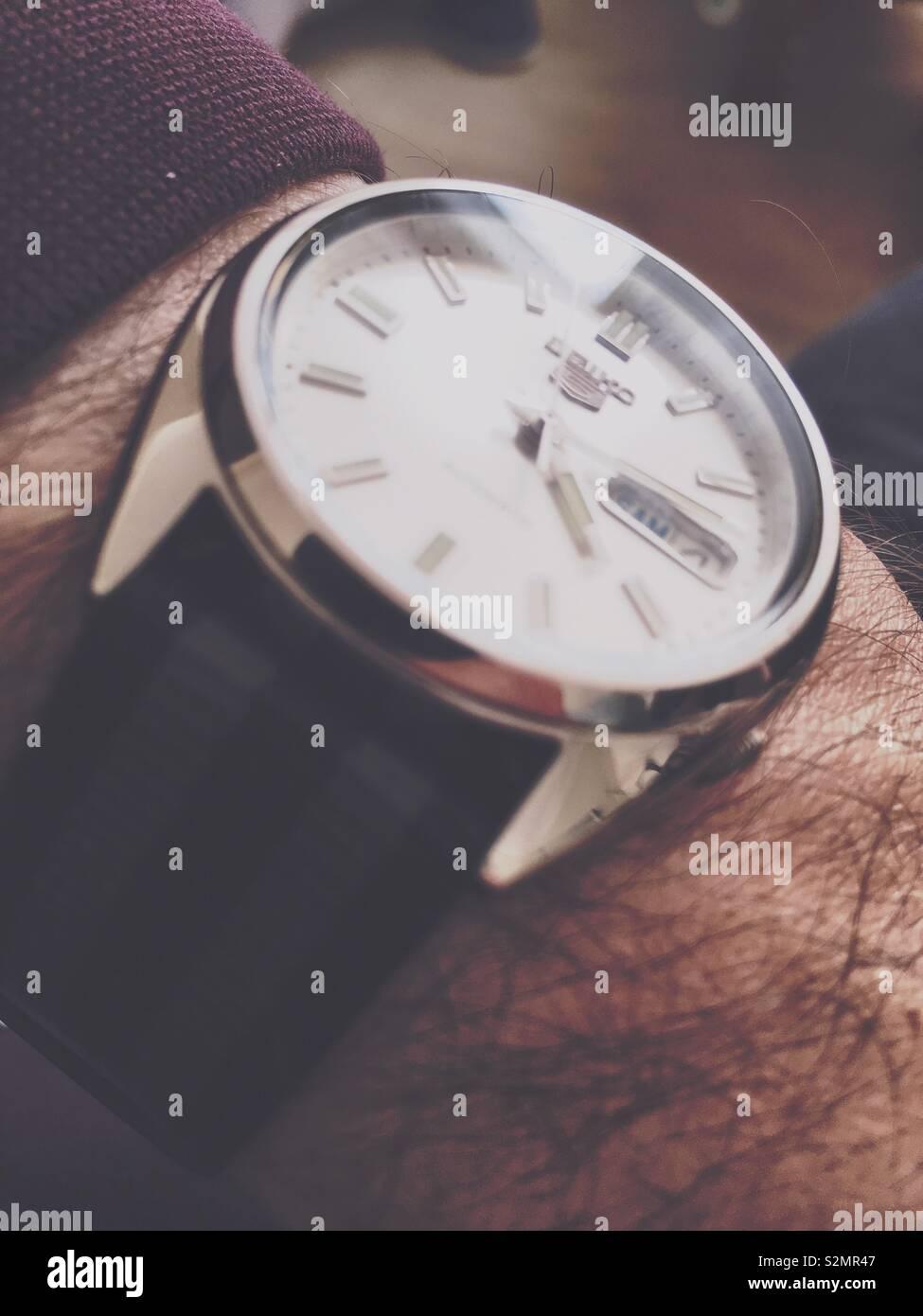Retro looking wrist watch on a mans wrist - Stock Image