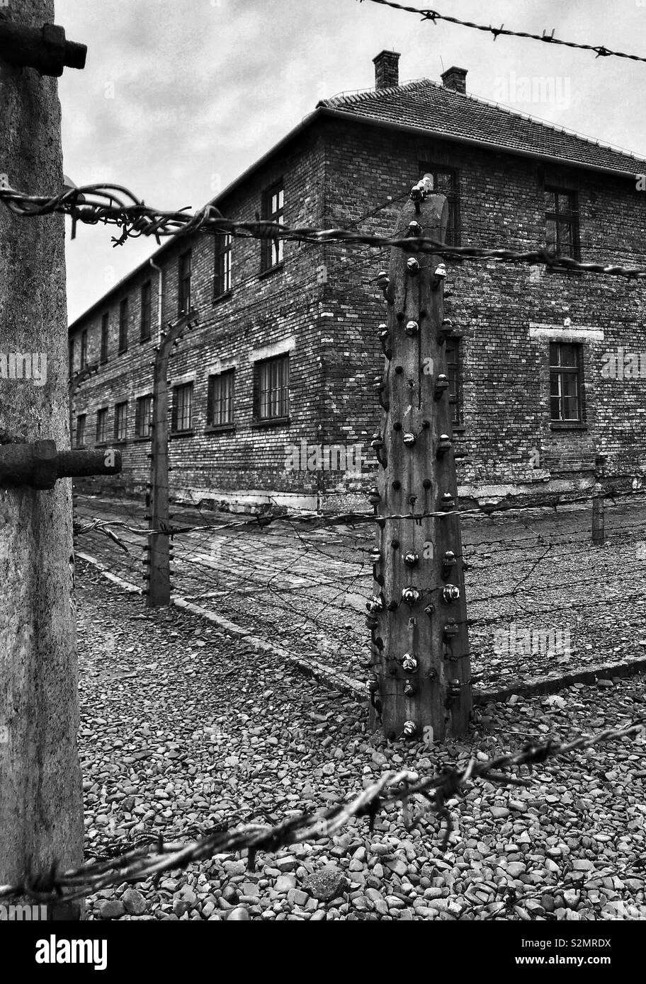 An exterior view of a building surrounded by electric fencing at the WW2 Nazi Auschwitz Concentration Camp in Oswiecim, Poland. Now a Memorial Museum & UNESCO World Heritage Site. © COLIN HOSKINS. - Stock Image