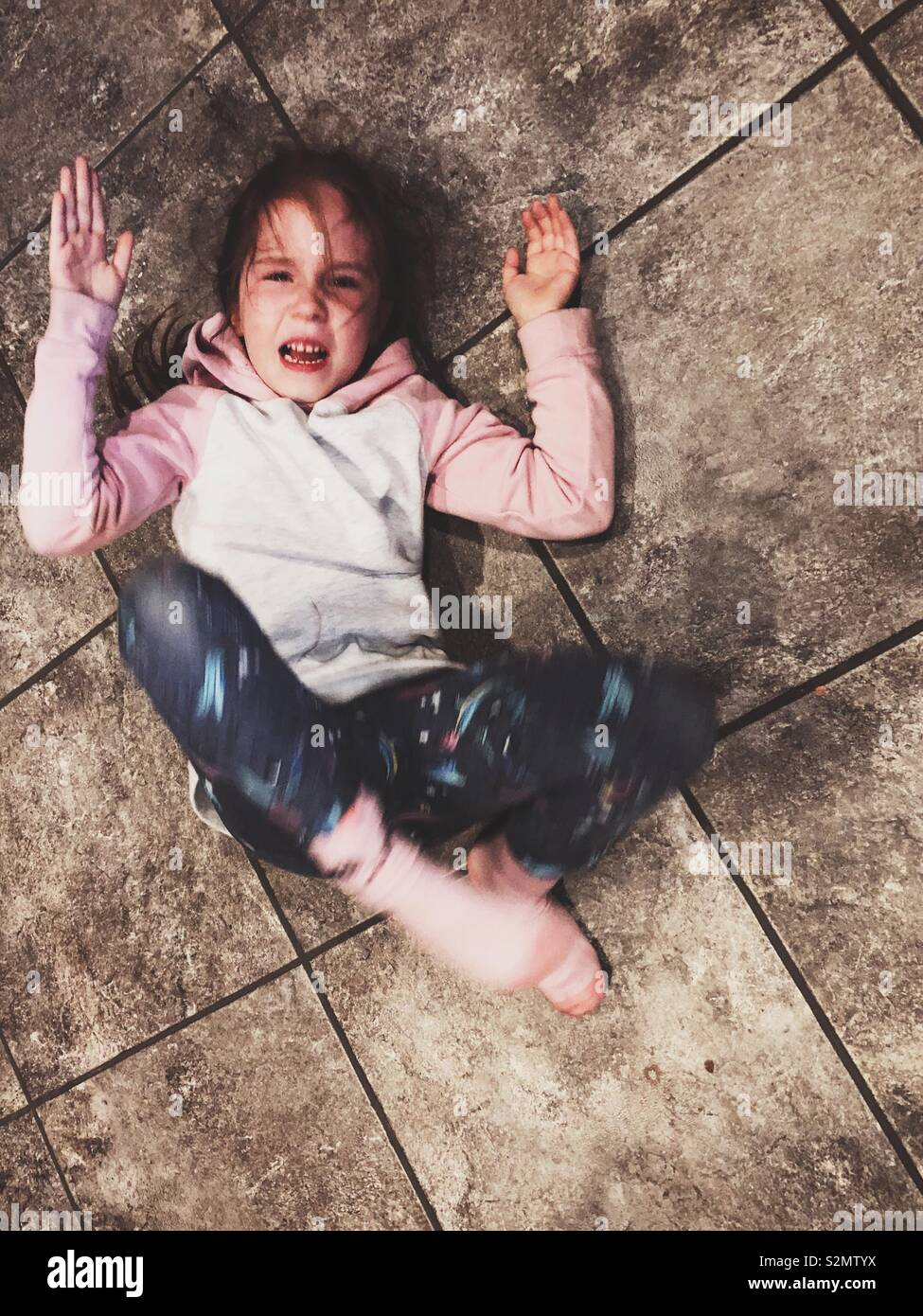 Young girl having a temper tantrum on the floor - Stock Image
