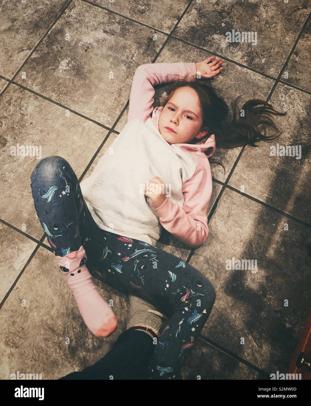 Angry young girl on the floor - Stock Image