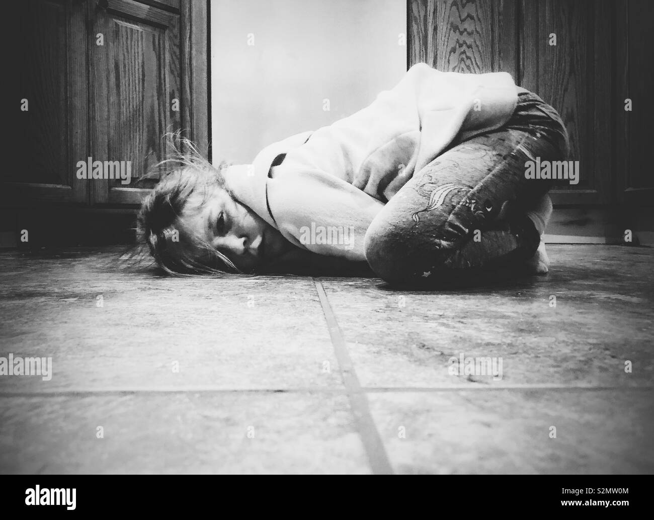 Moody image of young girl curled up on kitchen floor feeling sad and upset - Stock Image