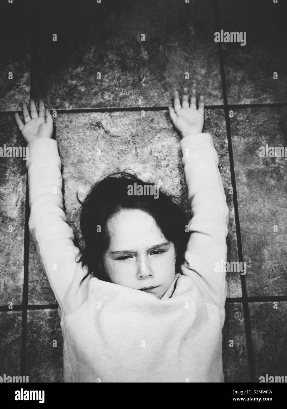 Angry young girl laying on tile floor with arms up - Stock Image
