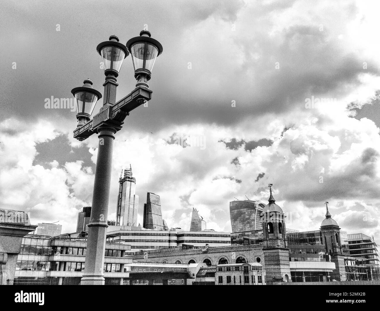 A view of the City of London skyline seen from Southwark bridge, over the River Thames, in London, England, UK. - Stock Image