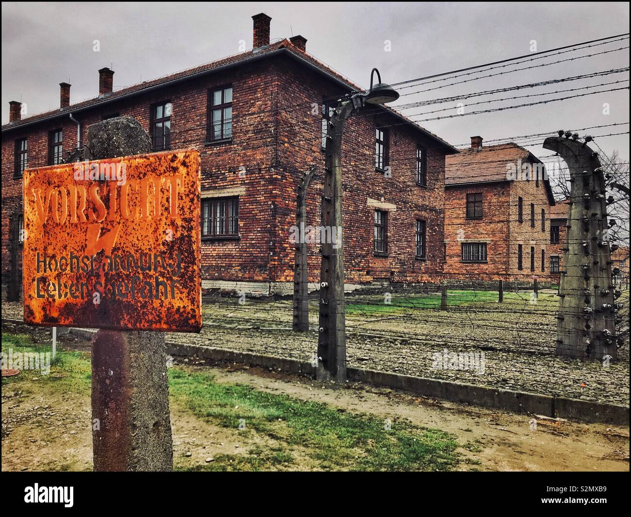 A sign @ the Nazi Auschwitz Concentration Camp warns inmates that the fence is electrified. Tens of Thousands of People (mostly Jews) were killed during here during the early 1940's. Now a UNESCO Site - Stock Image