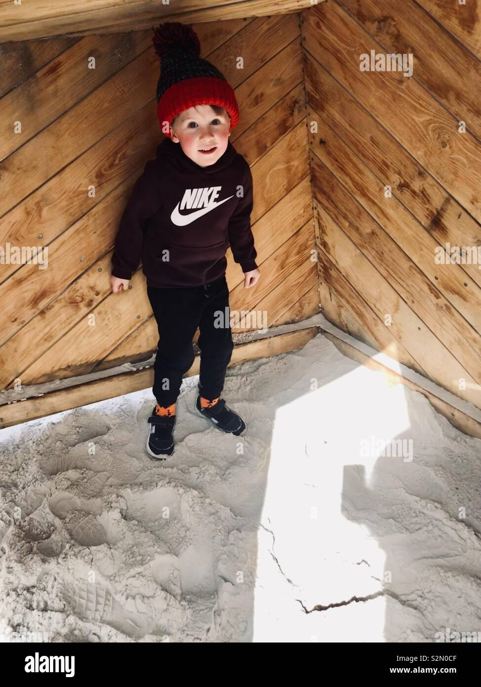 Boy hiding in crate at playpark - Stock Image